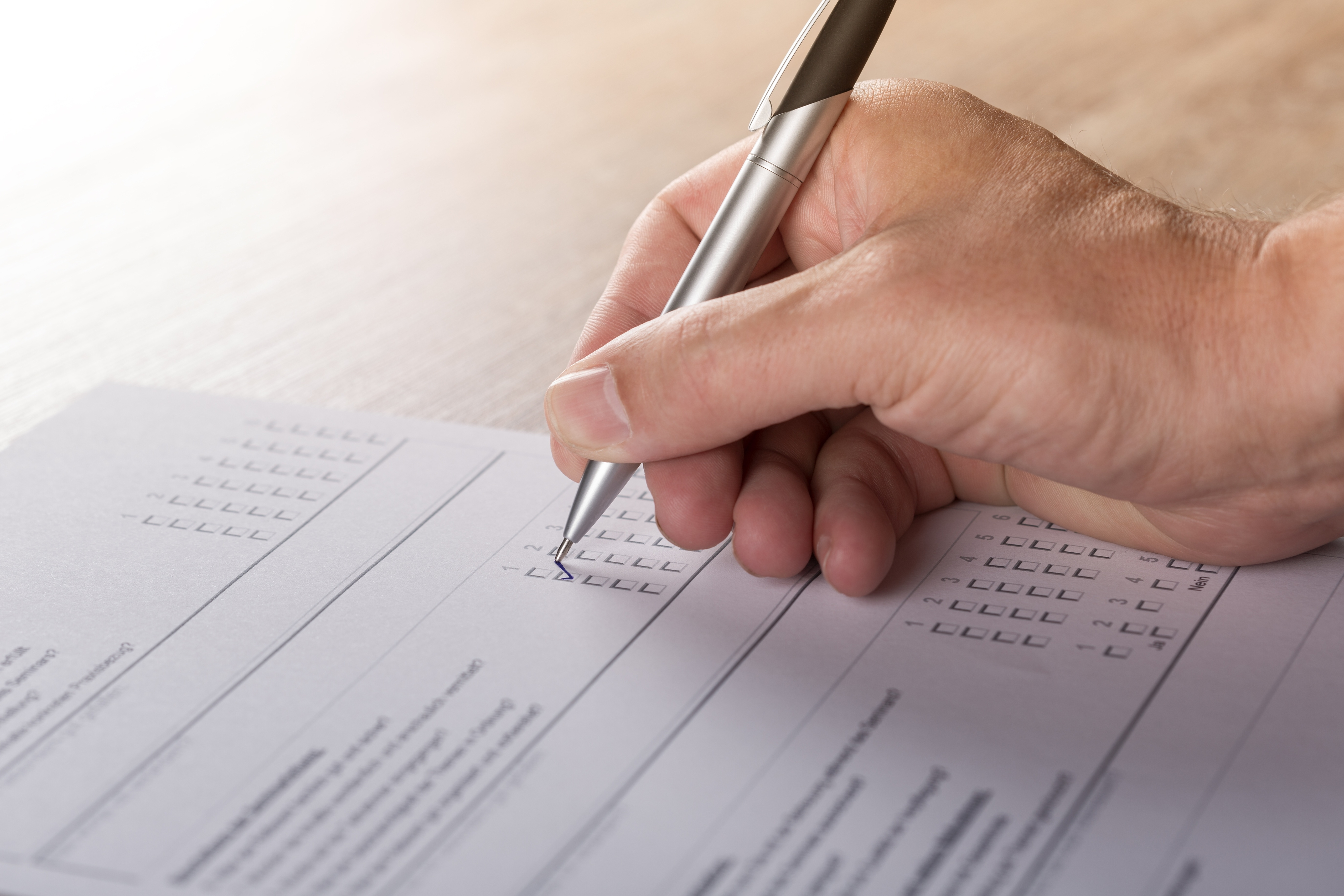photo of a hand filling out a questionnaire